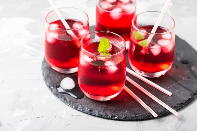 Красный алкогольный коктейль со льдом и мятой