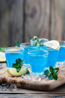 木製のテーブルにレモンとブルーキュラソーリキュール