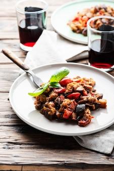 木製のテーブルに伝統的なシチリア茄子皿カポナータ