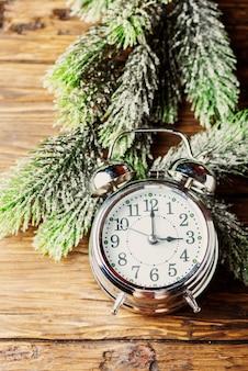 木の板に目覚まし時計と松の枝