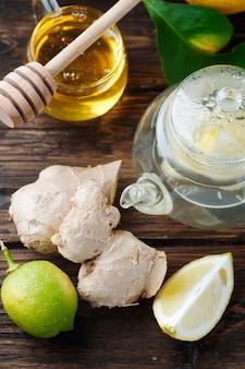 生姜、レモン、木製のテーブルの上に蜂蜜のカクテル