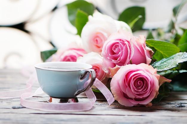ピンクのバラと木製のテーブルの上のコーヒー