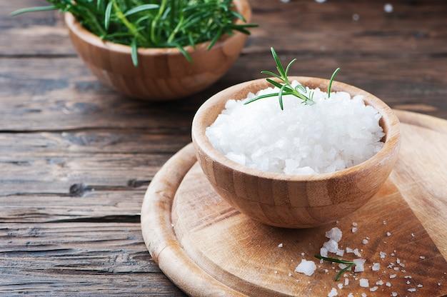 Морская соль и свежий розмарин на деревянном столе