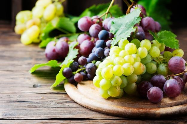 Черный и желтый виноград на деревянном столе