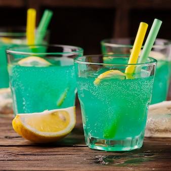 Зеленый коктейль с лимоном и льдом на деревянном столе