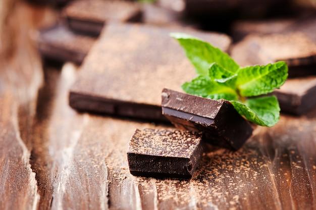 Темный шоколад и зеленая мята на деревянном столе