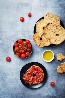 イタリア料理のコンセプトです。トマト、オイル、オリガノのフリゼル。コピースペース付きのトップダウンビュー