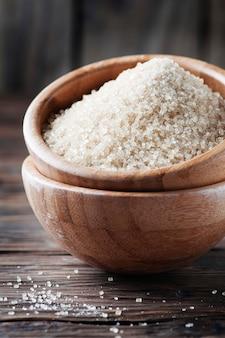 Коричневый сладкий сахар на деревянном столе, селективный фокус
