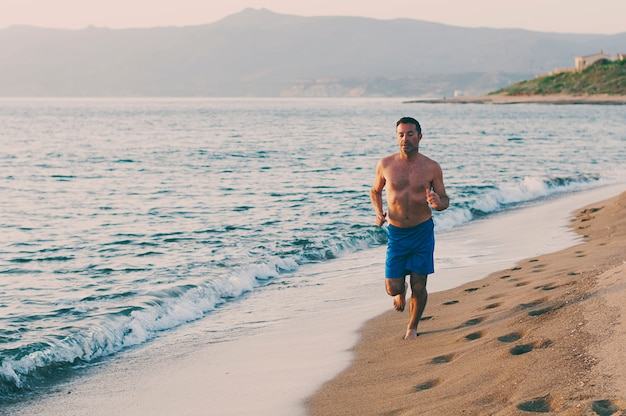 サンセットビーチで走っているハンサムな男
