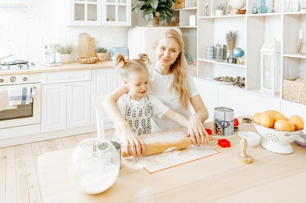 母親と幼い娘が自宅の台所で一緒にベーキング生地を準備します。