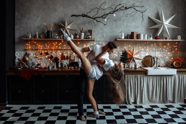 愛の美しいカップルは、新年やクリスマスのために装飾されたキッチンで抱擁します。