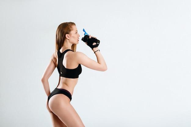 黒いスポーツウェア飲料水またはフィットネスシェーカーからタンパク質の女性