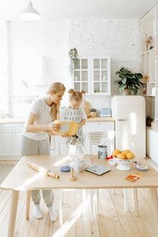 Мать и ее маленькая дочь вместе готовят тесто на домашней кухне.