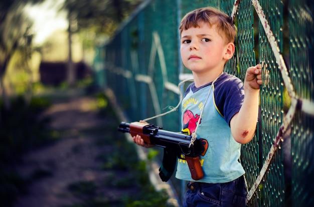 おもちゃの銃のマシンで小さな男の子