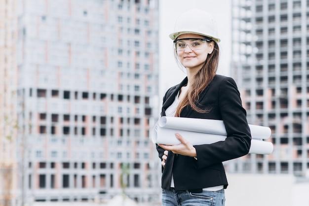 黄色の保護ヘルメットと保護眼鏡、建築の概念で美しい少女の肖像画を閉じます
