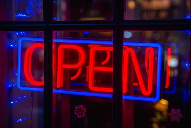 オープンサインは、カフェのドアのガラスを通して広がっています。ビジネスサービスと食べ物のコンセプト。ビンテージトーンフィルターカラースタイル。