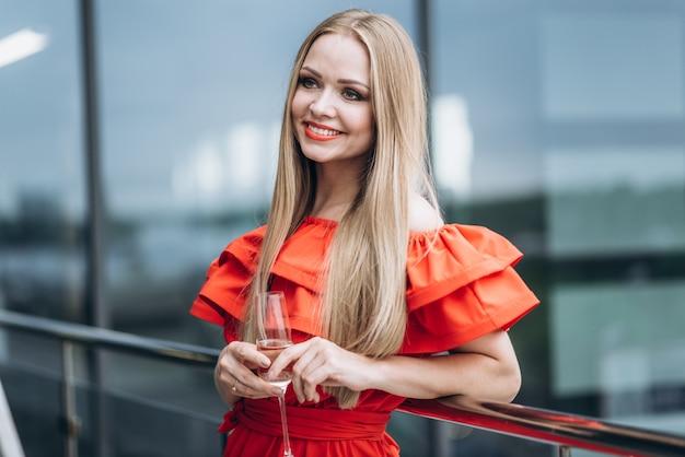シャンパンの一杯の赤いドレスで美しい女の子
