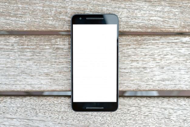 木製の背景に白い画面でモバイルスマートフォンモックアップ。