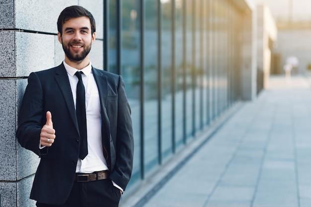 オフィスビルの背景にポーズを上げている笑顔のビジネスマンの肖像画の肖像