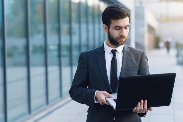 Бизнесмен на открытом воздухе на фоне городских пейзажей, держа ноутбук, глядя в него.