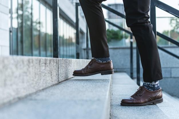 Крупный план мужских ног в деловых брюках и туфлях, идущих вверх по лестнице