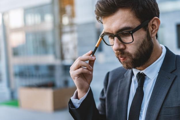 眼鏡の中の瞑想的な若い若い実業家が手にペンを持っています