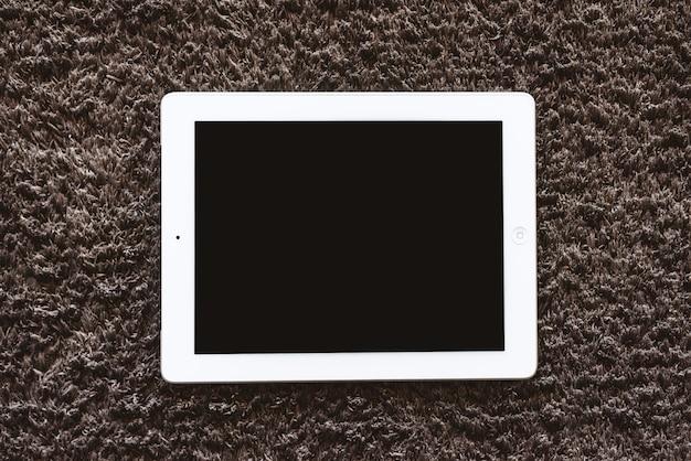 カーペットの上の床に横になっているタブレットモックアップ