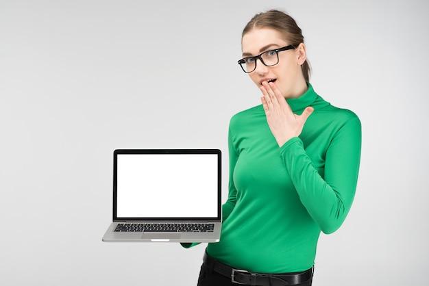 Студент девушка держит ноутбук в руках и удивлен