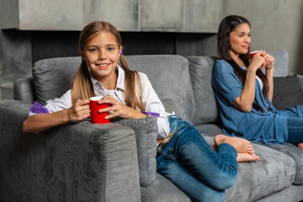 Счастливая девушка подросток и ее мать, улыбаясь и держа чашку чая