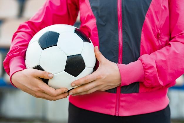 サッカーボールを保持している大人の手。スポーツウェアを着ている男性または女性