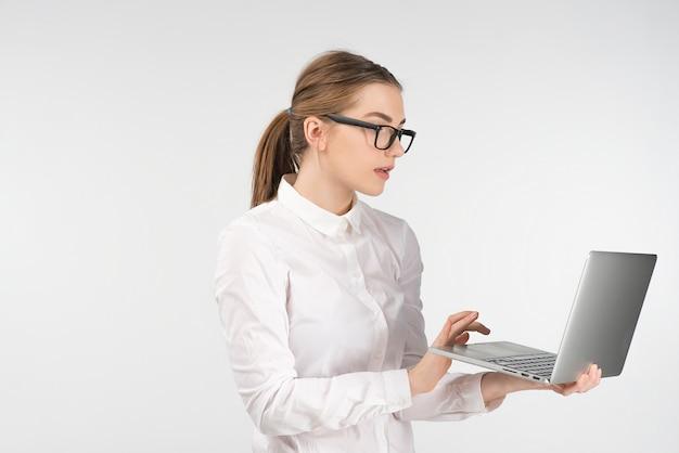 メガネの女性は立っている間ラップトップで動作します。画面をよく見て