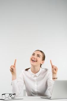 Счастливая женщина сидит рядом ноутбук и смеется смотрит вверх, указывая пальцем на нее обеими руками. - вертикальное изображение