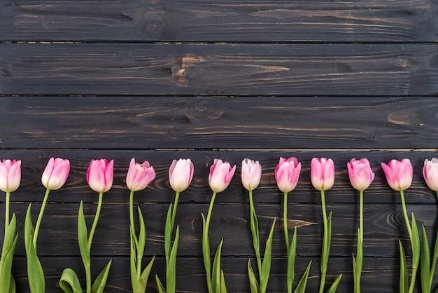 メッセージのコピースペースを持つ素朴な木製の背景にピンクのチューリップの行。