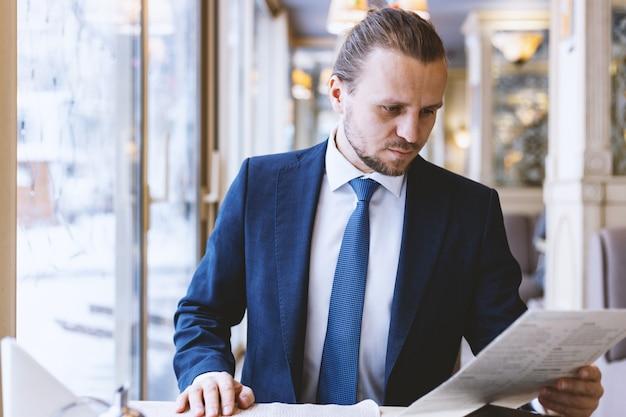 ビジネスマンがオフィスで書類を読みます。注意深くそして緊張した見方