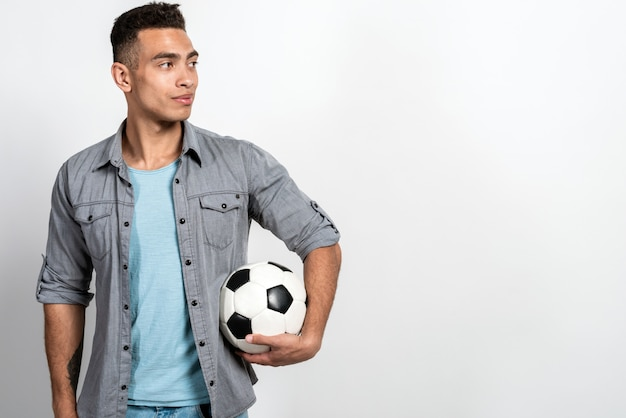 サッカーボールを持って立っているカジュアルな服を着てムラート男