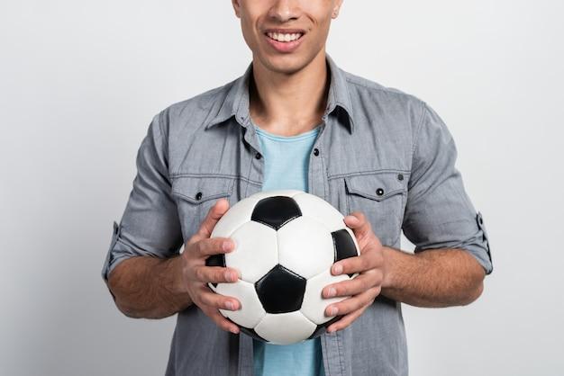 男性の手のクローズアップでサッカーボールに焦点を当てる