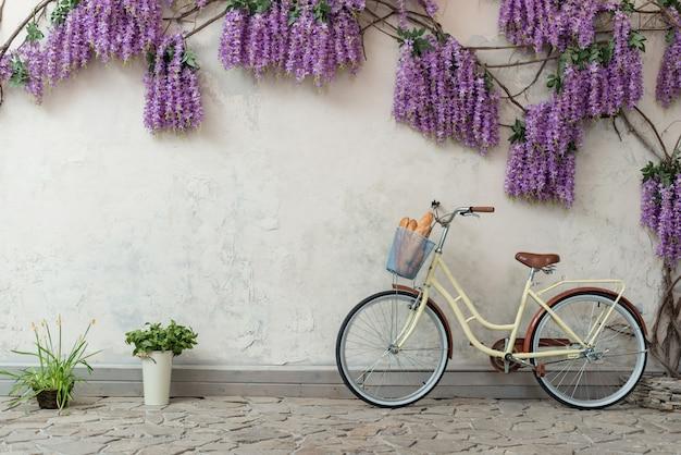 パンとバスケットを持つ自転車は紫色の花と灰色の背景に寄りかかった - 画像