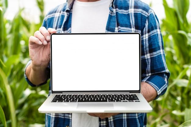 農夫は開いているラップトップを保持しているフィールドに立っています。ホワイトスクリーンモックアップ
