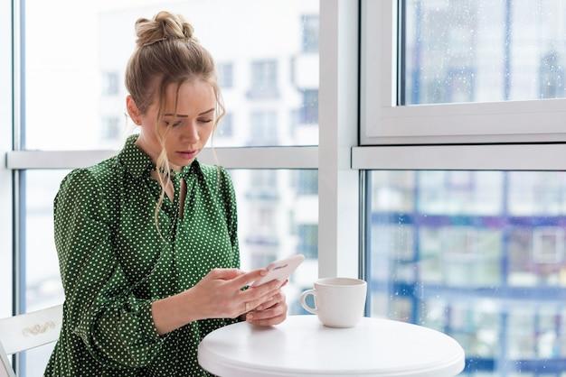 Поясной портрет блондинки сидит за столом рядом с окном, держит мобильный телефон и смотрит на экран
