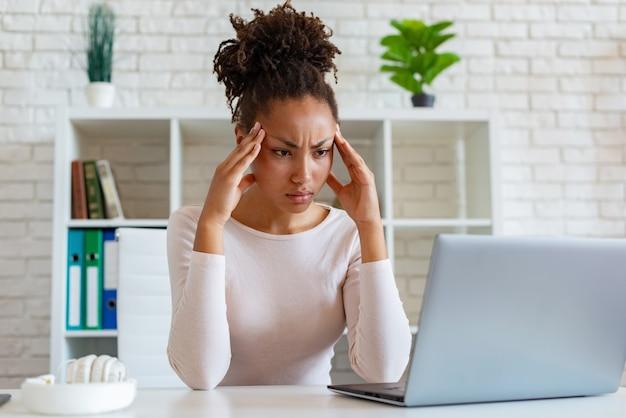 ムラートの女性はラップトップでの作業中に痛みを和らげるために寺院に触れる、慢性的な頭痛があります