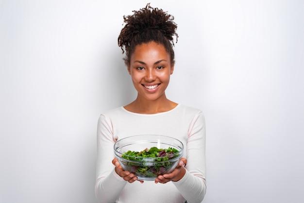 一杯のサラダのボウルと立っている女性のクローズアップの肖像画