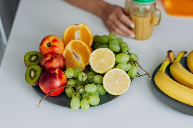 テーブルに横になっているフルーツの入り口を持つイメージ。スムージーのグラスを持つ女性の手