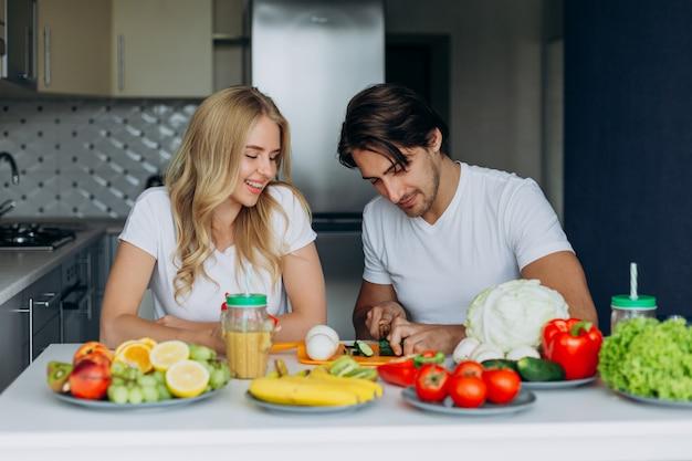 健康食品でテーブルに座って台所でカップル。男は野菜を切る