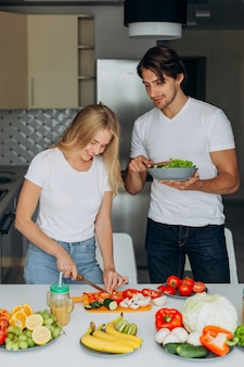 健康的な食品を調理する台所でカップル。サラダプレートを抱きかかえた
