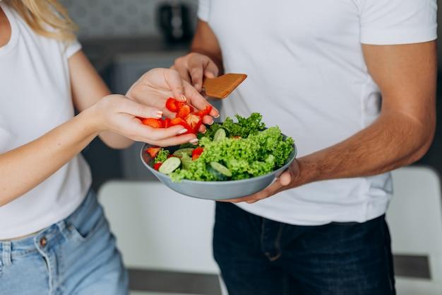 健康的な食品を調理するクローズアップの男性と女性の手。サラダプレートを抱きかかえた