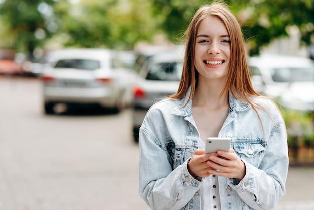 スマートフォンで立っていると屋外のカメラを見て笑顔の若い女性