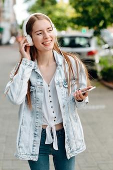スマートフォンを保持しているとイヤホン屋外で音楽を聴いて幸せな女の子