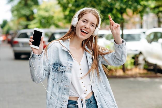 Возбужденная девушка слушает музыку в наушниках и танцует на улице, показывая смартфон