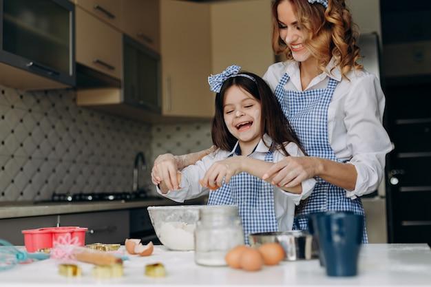 娘と彼女の母親は笑顔で卵を割る。
