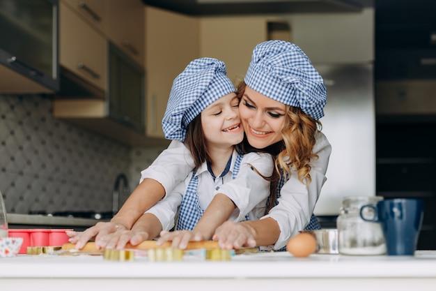 小さな女の子と母親は一緒に麺棒で生地をロールアウトします。